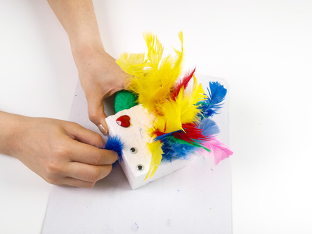 Little girls hands playing with colorful feathers, creating Easter decoration photo