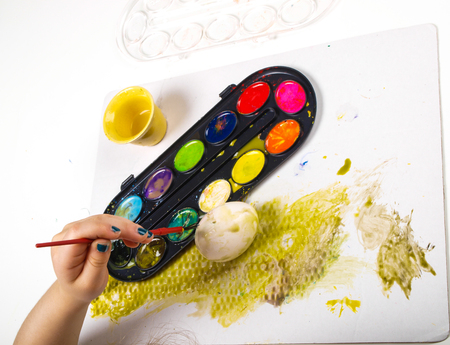 Little girls hands playing with colorful paint, creating Easter decoration Stock Photo