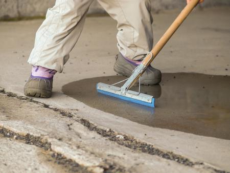 Niño drenar el agua del suelo de cemento húmedo con una fregona de goma Foto de archivo