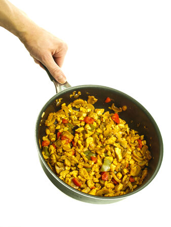 Fry pan with chicken with curry, red pepper and corn held by a male chef towards white background Stock Photo
