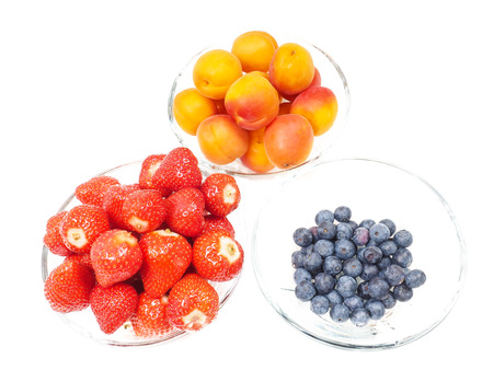 Strawberry, apricot and blueberries in glass bowls towards bright background