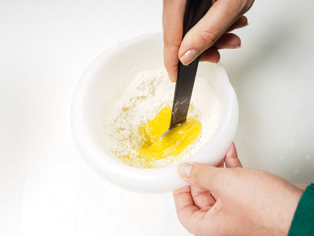 Female person blending flour with egg yolk and melted butter with a black spatula in plastic bowl Stock Photo