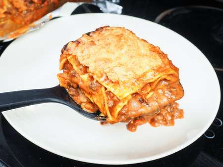 plating: Someone plating fresh lasagna onto porcelain plate with black spatula