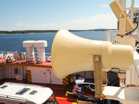 Speaker attached onto railing on boat above cars on deck