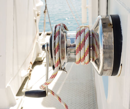 hand crank: White and red rope on winch with hand crank on a vessel