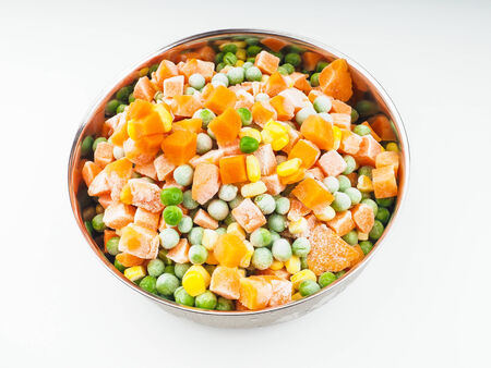 thawing: Frozen carrots, maize and peas, thawing in a steel bowl Stock Photo