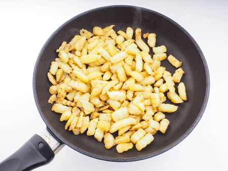 Frying chopped potatoes in a fry pan isolated photo