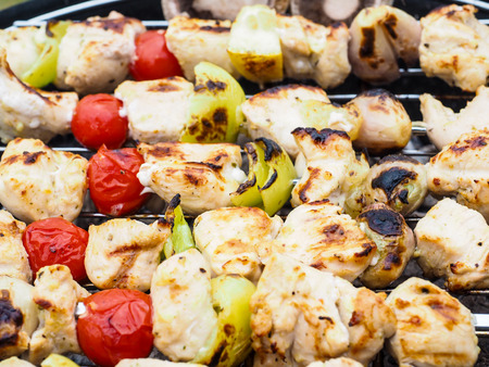 barbecuing: Barbecuing chicken, vegetables on spear over charcoal grill Stock Photo
