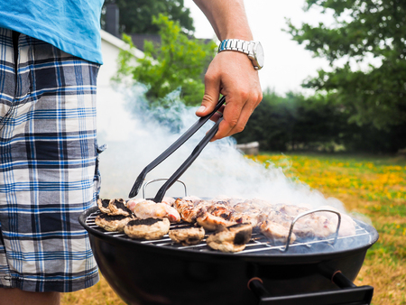 Male person with food tweezers barbequing with lots of smoke photo