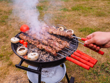 Closeup of a chef turning skewers of meat on hot barbecue Stock Photo