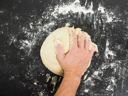 Hands kneading dough on black board with flour photo