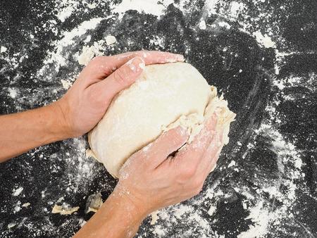 Hände kneten Teig auf schwarzem Karton mit Mehl