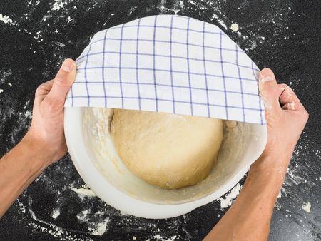 proving: Person covering a dough for proving in a bowl on black table Stock Photo