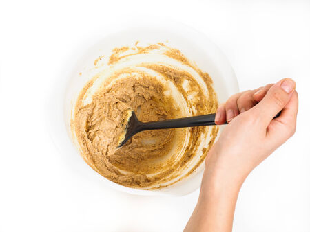 Person siring a bake mix in white plastic bowl with black spatula towards white photo