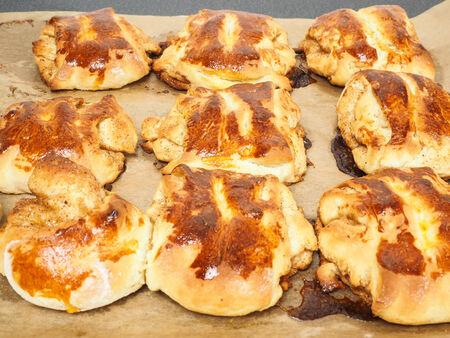 Fresh made cinnamon buns plaited on baking paper photo