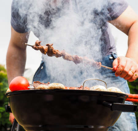 Chef covered in smoke grilling skewers of meat and vegetables over charcoal barbecue photo