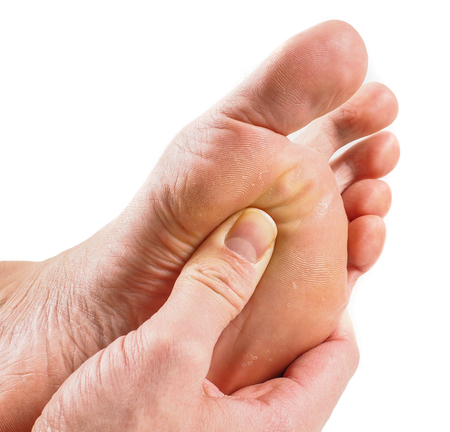 Male person receiving podiatry with pressure point technique under foot isolated towards white