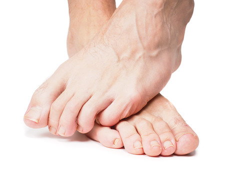 feet naked: Male feet one over the other isolated towards white
