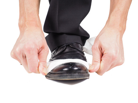 Closeup of male shining black leather shoes with a sheet of white tissue towards white background photo