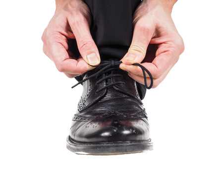 Closeup of male hands tying shoelaces on black leather shoes wearing suit towards white photo