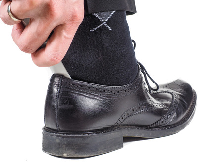 Male hand entering foot with black sock into black leather shoe with shoehorn towards white Stock Photo