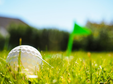 Golf ball laying in rough green grass approaching the tee with green flag photo