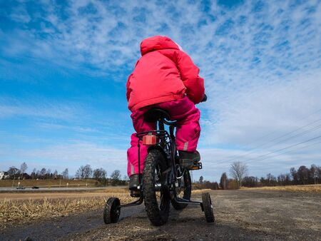 Little girl biker on gravle road with supporting wheels on gravel road at spring with blue sky