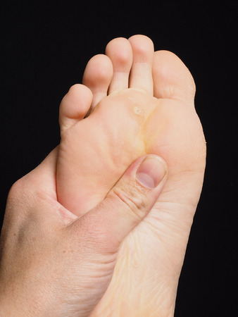 Pressure point massage under foot with thumb isolated towards black Stock Photo