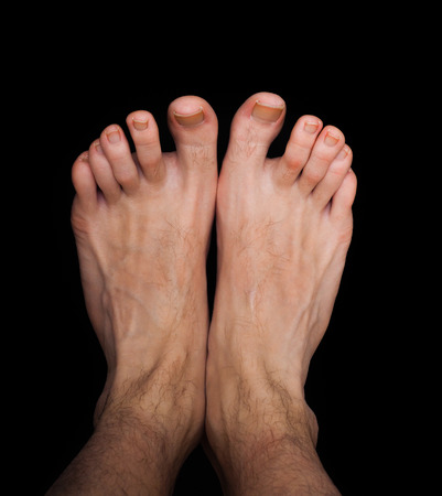 bare foot: Pair of caucasian male feet isolated towards black Stock Photo