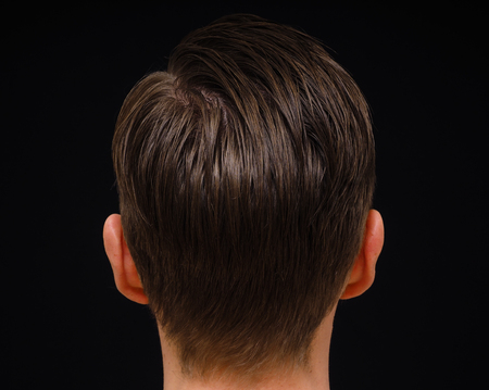 Rear view of hairstyle on male person with brown hair at closeup isolated towards black background