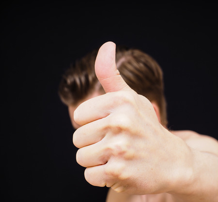 Caucasian male showing thumbs up covering face isolated on black