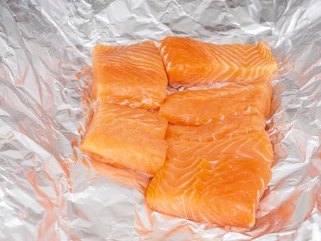 preperation: Closeup of unseasoned salmon pieces in aluminum foil