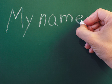 my name is: Person writing on green chalkboard; My name, with calk