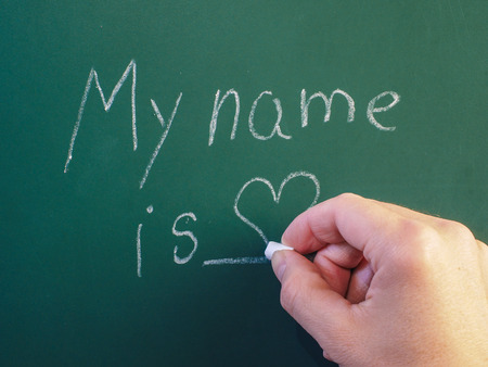 person writing: Person writing on green chalkboard with calk Stock Photo