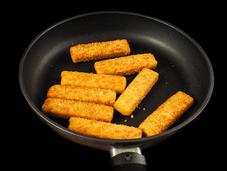 Crumbed fish fingers in fry pan, isolated on black