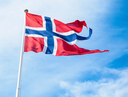The Royal flag of Norway on a pole towards blue and white sky in daylight