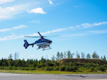 autoridades: Helic�ptero de la Polic�a de las autoridades noruegas aspiradora sobre el campo de aterrizaje Foto de archivo