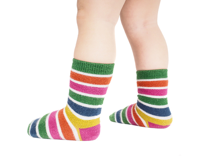 leg: Toddler standing in striped socks and bare legs isolated on white