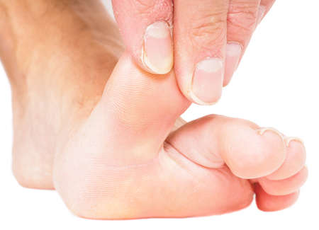touching toes: Male person pulling big toe backwards isolated towards white Stock Photo