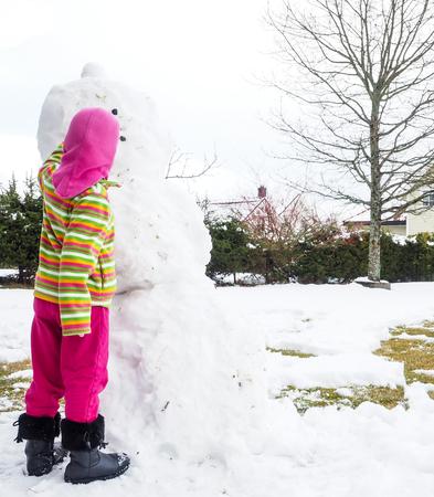 pink hat: Girl making snowman in garden, hiding under pink hat Stock Photo
