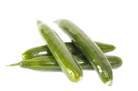 Cucumbers in heat shrink film, in a pile, isolated towards white background