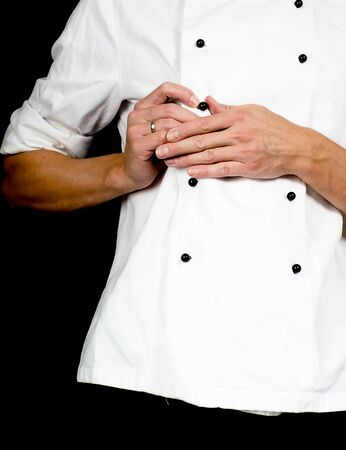 Professional chef buttoning up a white chefs jacket towards black