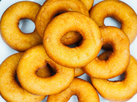 Closeup of a plate with freshly made dark brown doughnuts Stock Photo