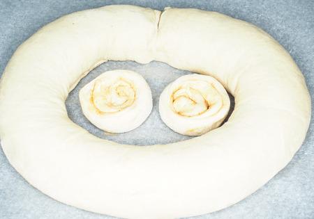 Closeup of raw cinnamon roll and cinnamon buns on baking paper