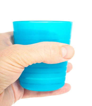 Empty blue plastic glass, held in a male persons hand