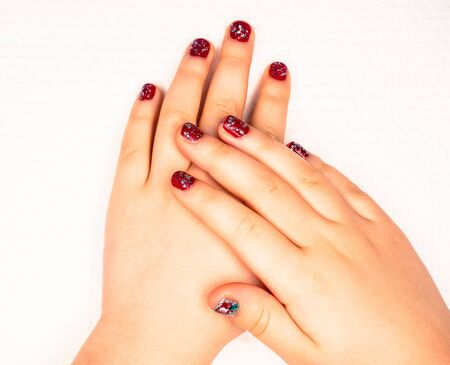 Little girl with beautiful manicure in dark pink, towards white paper Stock Photo