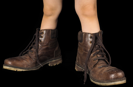 Kid wearing a pair of too big untied and unpolished brown leather boots, on black Stock Photo