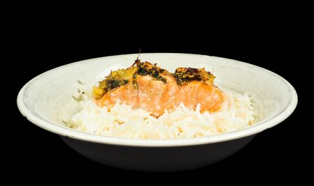 towards: Delicious piece of salmon on a bed of long grained rice, in a deep plate towards black