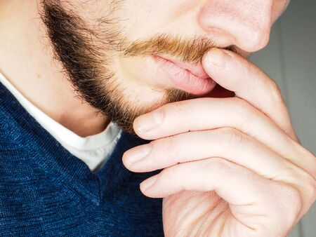 Male person, at closeup with fingers in beard Stock Photo