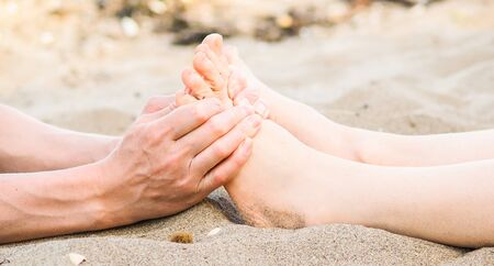 Foot massage on a beach in sand, male and female caucasian